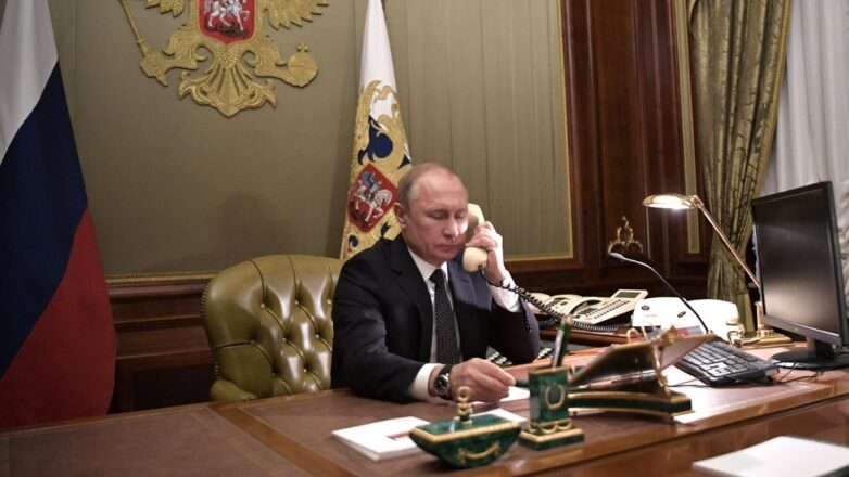Президент Российской Федерации Владимир Путин говорит по телефону герб