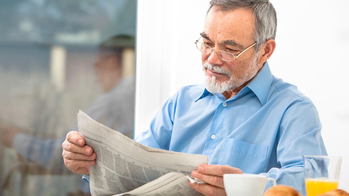 Пожилой человек читает газету за завтраком