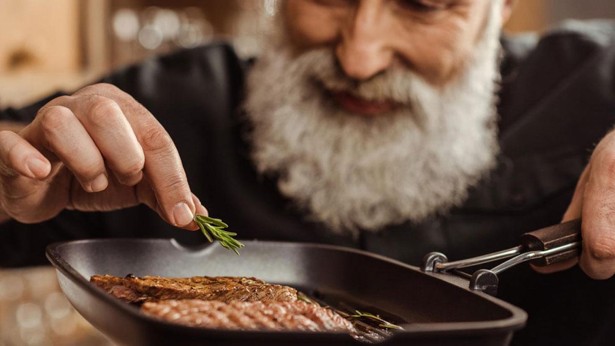 пожилой мужчина готовит стейк
