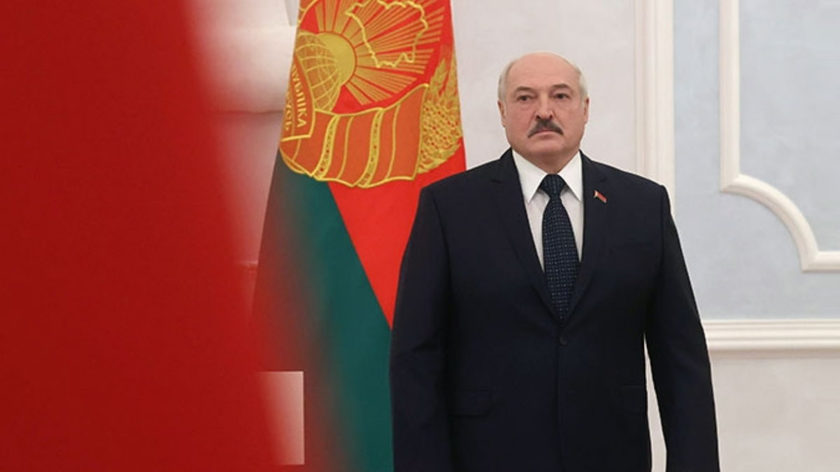 Александр Лукашенко на фоне флага два