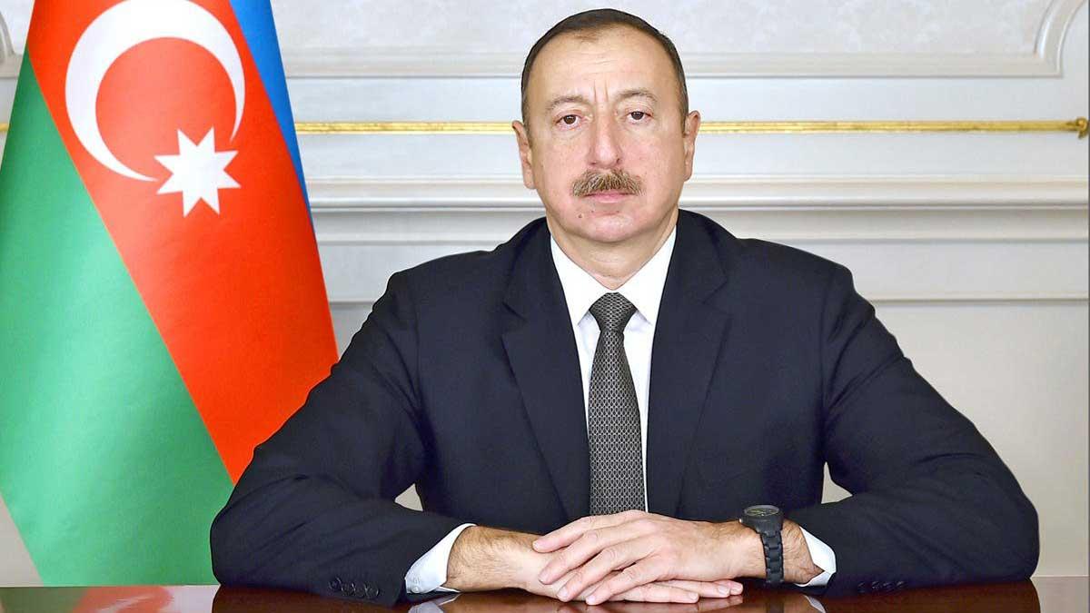 Президент Азербайджана Ильхам Алиев за столом с флагом