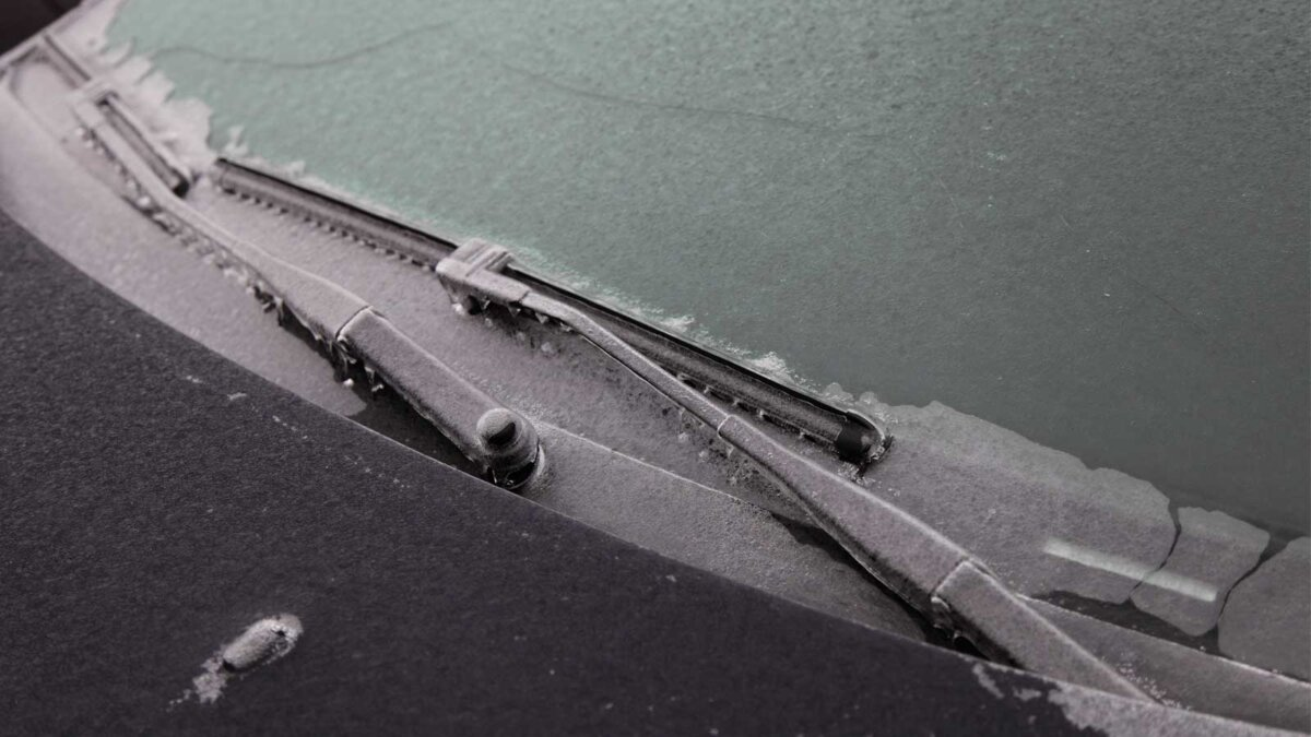 Покрытые льдом автомобильные дворники на ветровом стекле крупным планом