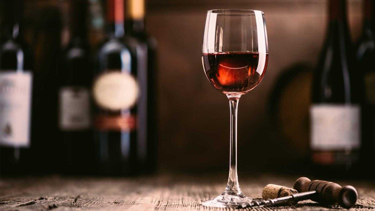 красный бокал вина и коллекция отличных вин на фоне