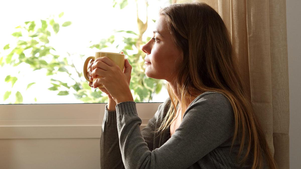 Женщина пьет кофе у окна