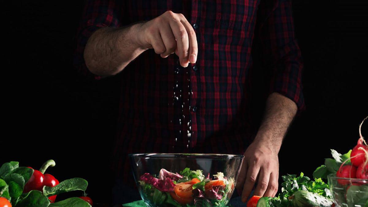 мужчина солит салат
